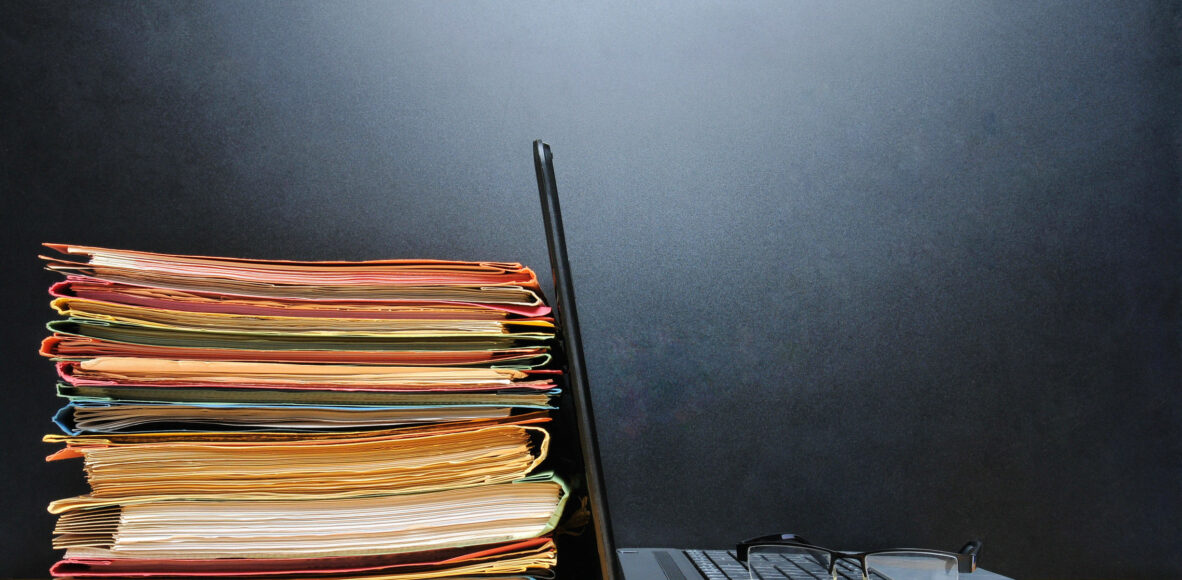 28035811 - laptop and office files on wooden table in front of black wall