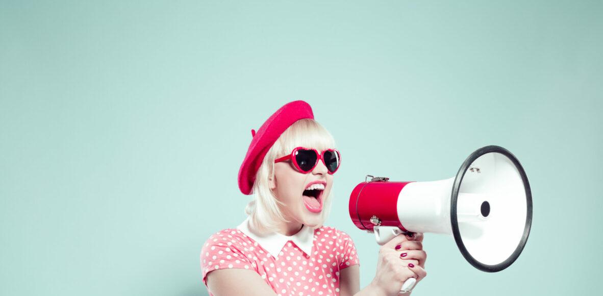 Cute blonde young woman shouting into megaphone